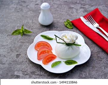 Fresh farm cheese burrata on a white curly plate on a gray concrete background. Served with chopped tomatoes. Italian food