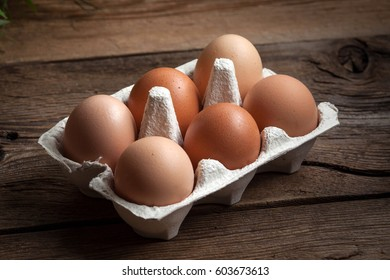 Fresh farm eggs on a wooden rustic background. Dark light.