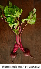 Fresh from the farm raw beets with tops on dark rustic wooden background from overhead in vertical format.  Healthy local food concept.
