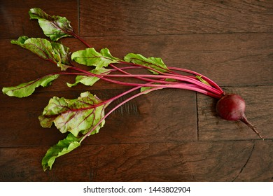 Fresh from the farm raw beets with tops on dark rustic wooden background from overhead in horizontal format.  Healthy local food concept.