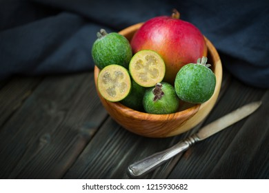 Fresh feijoa (Acca sellowiana) and ripe mango in a wooden bowl closeup. Selective focus.