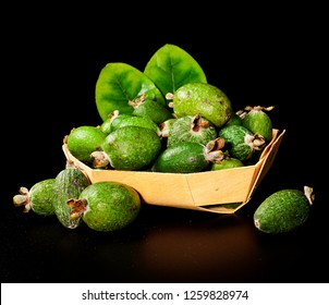 Fresh feijoa fruits (acca sellowiana, pineapple guava) in a wooden basket on a black background