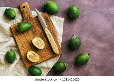 Fresh feijoa fruits on a cutting board, dark rustic background. Top view, flat lay