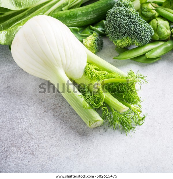 Fresh fennel with assorted green vegetables, salad, broccoli, cucumber, peas and Brussels sprouts on light gray stone table top. Healthy food concept with copy space.