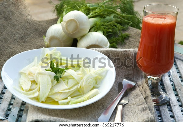 Fresh fennel salad and a glass of fresh carrot juice