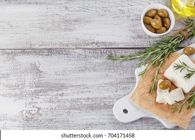 Fresh feta cheese with green olives, olives oil and rosemary on white wooden serving board over light wooden background. Top view, free space for text