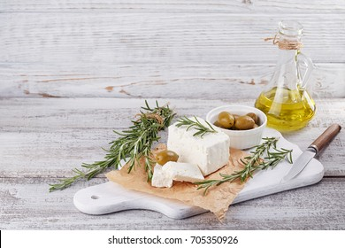 Fresh feta cheese with green olives, olives oil and rosemary on white wooden serving board over light wooden background. Free space for text
