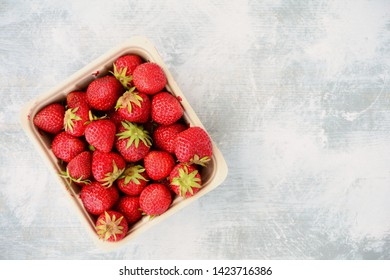 Fresh from the  field lush ripe strawberries on rustic wooden background in flat lay composition with spoons with room for your text.