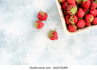 Fresh from the  field lush ripe strawberries on rustic wooden background in flat lay composition with room for your text.