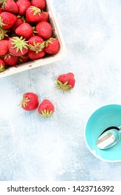 Fresh from the  field lush ripe strawberries on rustic wooden background in flat lay composition.  Little aqua bowls with spoons with room for your text.