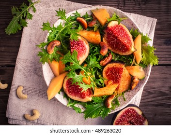 Fresh fig and melon salad with mizuna and smoky cashews top view