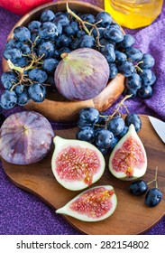 Fresh figs and dark grape with honey on table