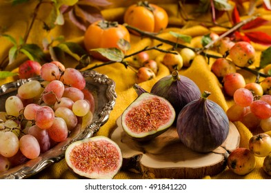 Fresh figs on the Board. Grapes on a vintage silver platter. Yellow background. Apples. Persimmon. Yellow and scarlet leaves. The autumn harvest.