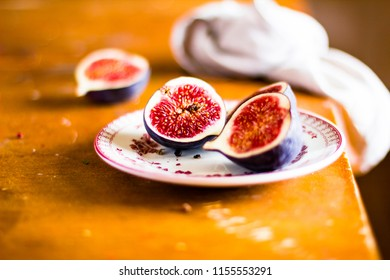 Fresh figs on a plate on a wooden table, selective focus. Autumn still life. Fresh fruits. Healthy and organic food.