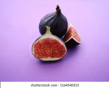 Fresh figs on a purple background. Sliced figs inscribed in a creative way. Food photo. From aside. Copy space