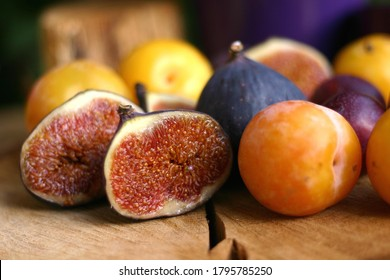 fresh figs and plums, juicy figs and plums closeup, autumn fruits on wooden board, sweet fruits, vegetarian food
