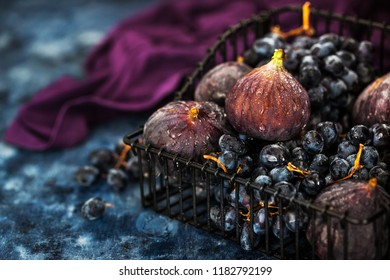 Fresh figs and purple grape in basket on dark wooden background
