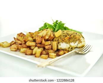 Fresh fillet of Atlantic cod with midro roast potatoes roasted in goose fat with rocket salad garnish, shot against a white background with generous accommodation for copy space.