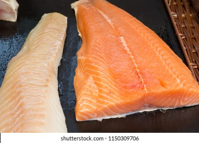 Fresh fillet of salmon and cod at a fishmonger on black slate