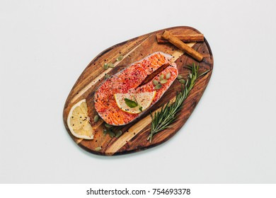 Fresh fillets of salmon with lemon, rosemary and spices on wooden background. steak sliced for the menu.  Preparation for cooking fish. Healthy and diet food. omega 3 oil, sea salt, top view, close up