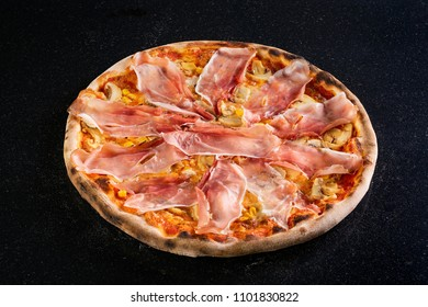 Fresh fine pizza with prosciutto slices on black marble table background