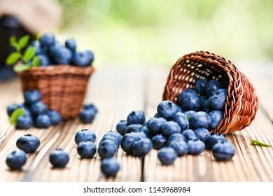 Fresh finest blueberries in small wicker basket. Few blueberry sprinkled or leaved on rustic table.