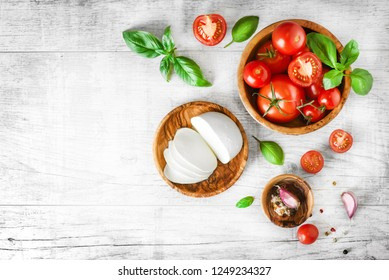 Fresh finest tomatoes on white rustic table with basil and mozzarella cheese top view. Tomato on old cut board.