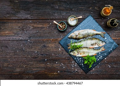 Fresh fish with aromatic herbs, spices, salt, bottles with olive oil and balsamic vinegar,perch on slate tray on a wet dock, on dark vintage background, top view, healthy food, diet or cooking concept