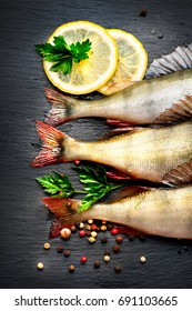 Fresh fish with aromatic herbs, spices, salt. Raw perch fish on slate tray dark vintage background, top view, preparing healthy food, cooking, diet, nutrition concept