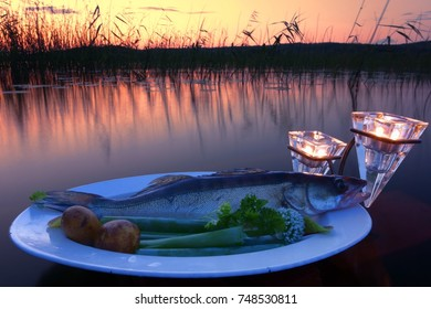 Fresh fish catch (pike perch) on plate served with fresh vegetables in outdoors setting on a lake with candles as a decoration at sunset time on summer evening at Nokia, Finland.