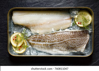 Fresh fish, cod fillets on ice with lemon slices, dill and red peppercorns, top view, horizontal setting