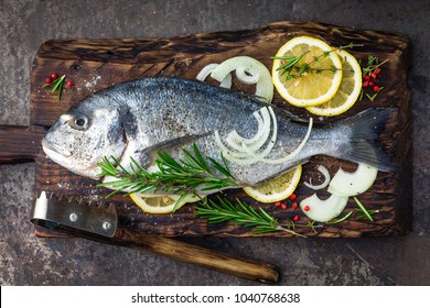 Fresh fish dorado with ingredients for cooking on wooden board. Raw sea bream or dorada fish on dark vintage metal background. Dietary food. Top view