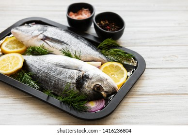 Fresh fish dorado. Dorado and ingredients for cooking on a table.