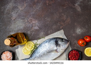 Fresh fish dorado and ingredients for cooking. Raw fish dorado with aromatic spices, herbs, lemon and vegetables on dark stone table. Top view, copy space