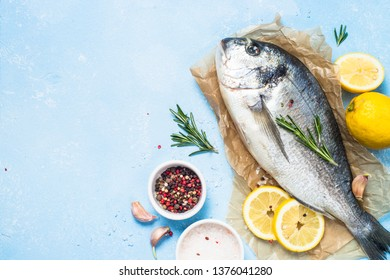 Fresh fish dorado on blue background with lemon, rosemary and spices. Top view with copy space.