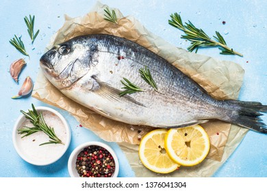 Fresh fish dorado on blue background with lemon, rosemary and spices. Top view.
