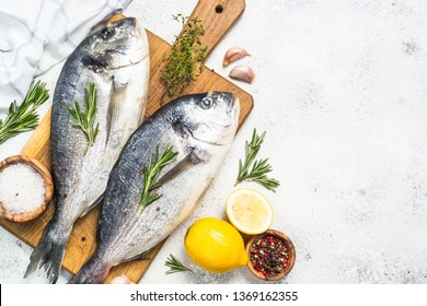 Fresh fish dorado fish on cutting board on white table with ingredients for cooking. Top view with copy space.