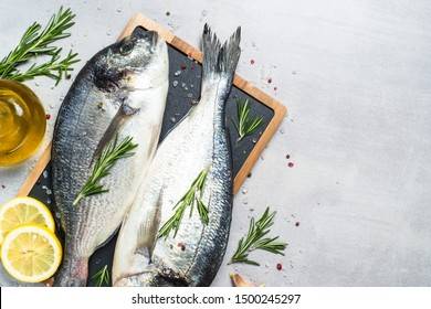 Fresh fish dorado on light stone background with lemon, rosemary and spices. Top view with space for text.