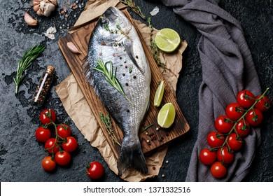 Fresh fish dorado. Raw dorado fish and ingredient for cooking. Fresh fish gilt-head bream dorade with salt, herbs and pepper.