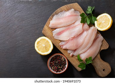 fresh fish fillet of tilapia with ingredients for cooking on wooden board, top view
