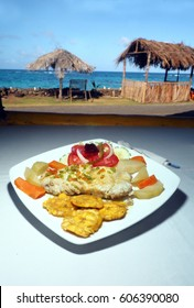 fresh fish fillet with tostones, salad and native vegetables is seen with Caribbean background in Big Corn Island, Nicaragua