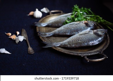 fresh fish gilthead served with parsley and garlic on the plate
