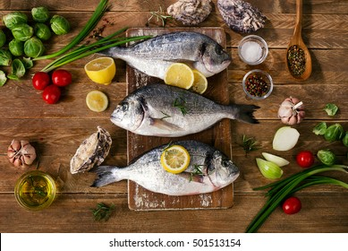 Fresh fish with herbs, spices and vegetables on a wooden background. Healthy food concept. Top view