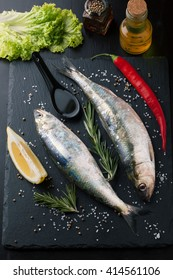 Fresh fish herring with spices, lemon and salt on a wooden background