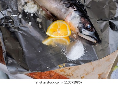 Fresh fish. Mackerel with salt, lemon and spices on  foil background. Top view