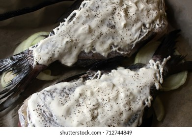 Fresh fish with mayonnaise, onion and flavoring prepared for baking.