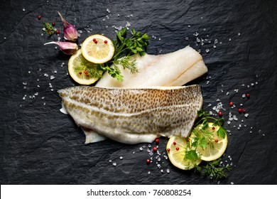 Fresh fish,  raw cod fillets with addition of herbs and lemon slices on black stone background, top view