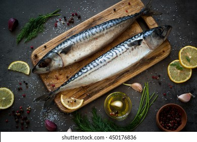 Fresh fish. Raw mackerel with salt, lemon and spices on a dark background.
