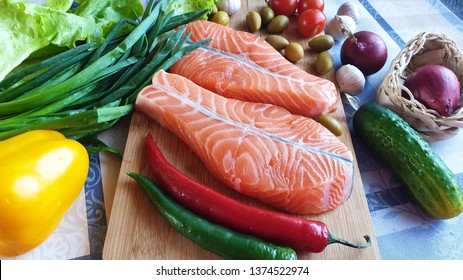 Fresh Fish  Raw Salmon Two  steaks with ingredients vegetables and spices  tomatoes  lemon and olives cucumber green salat onion garlic lime  Healthy food diet concept