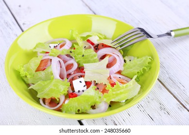 Fresh fish salad with vegetables on plate on wooden table close-up